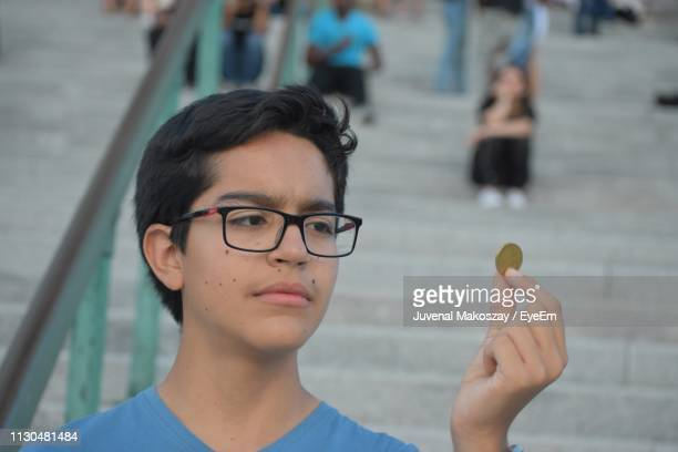 Close-Up Of Boy Holding Coin Against Steps In City