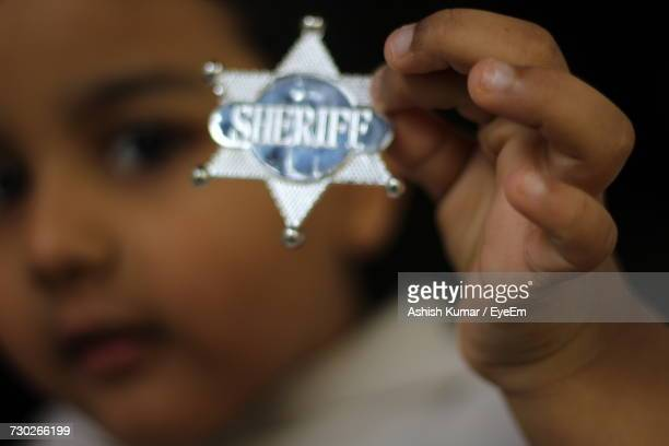 Close-Up Of Boy Holding Metallic Star Shape With Text