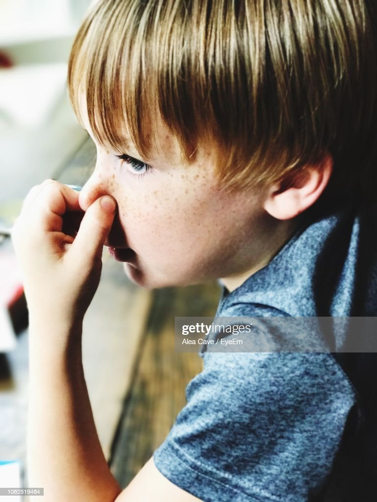 Close-Up Of Boy Holding Nose : Stock Photo