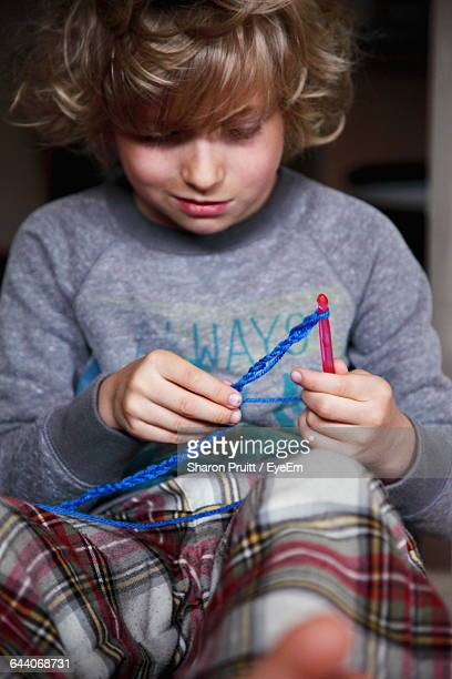Close-Up Of Boy Knitting Wool With Needle At Home