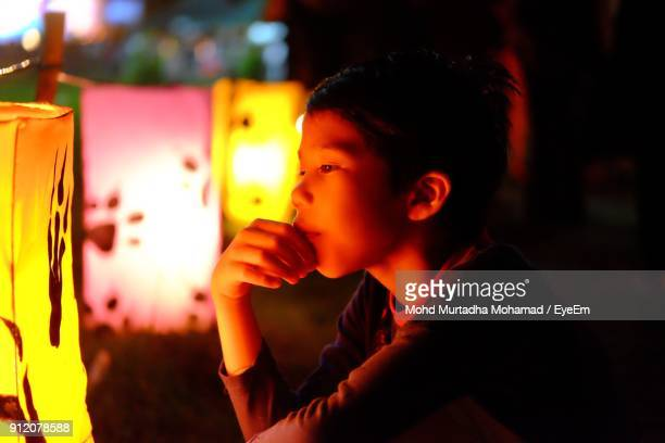 Close-Up Of Boy Looking At Illuminated Lantern