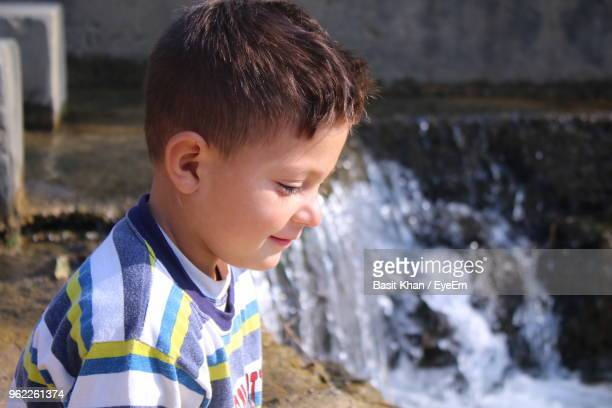 Close-Up Of Boy Looking Away While Sitting Against Waterfall