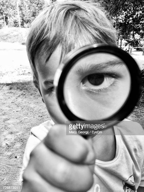 Close-Up Of Boy Looking Through Magnifying Glass On Field