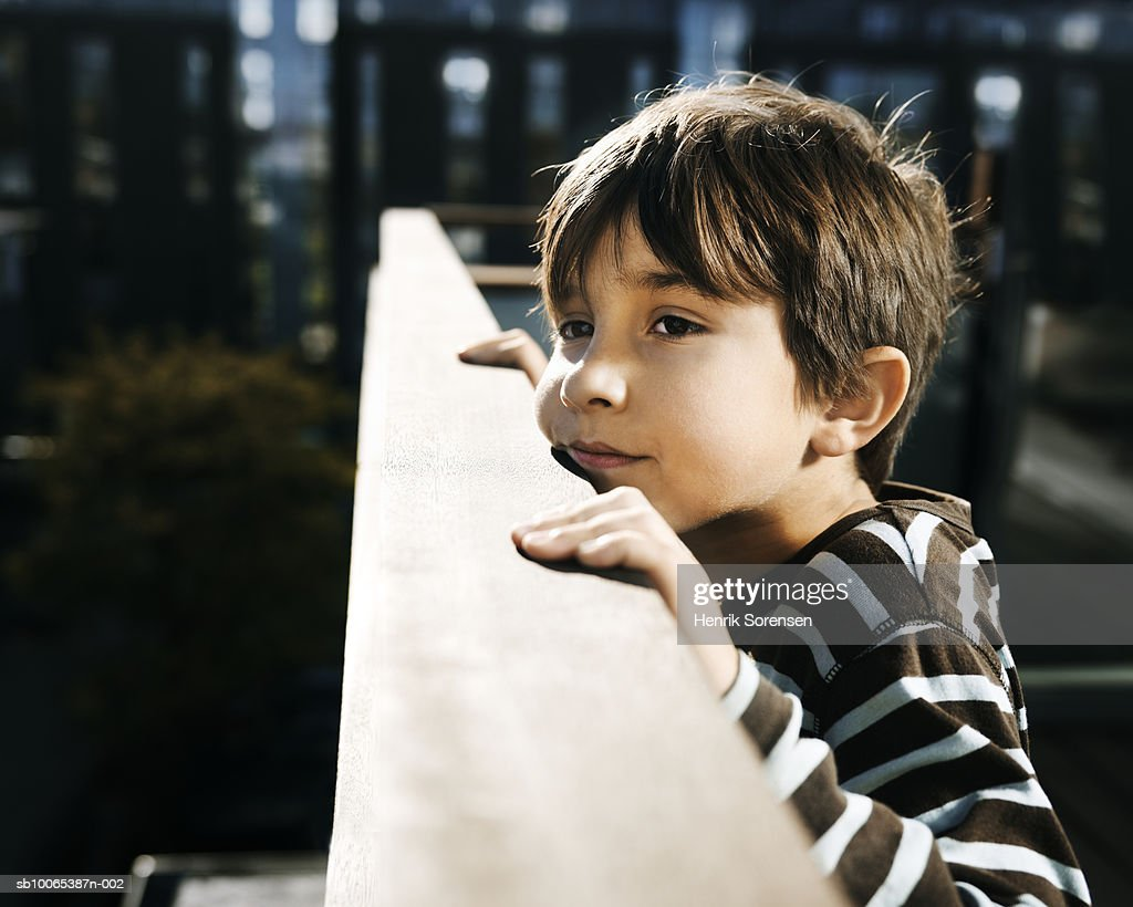 Close-up of boy (8-9) on balcony, leaning on railing : Foto stock