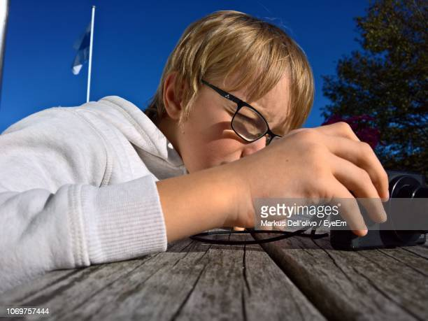 Close-Up Of Boy Photographing Through Camera At Table Against Sky