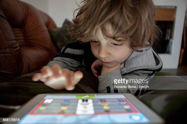 Close-Up Of Boy Playing With Digital Tablet At Home
