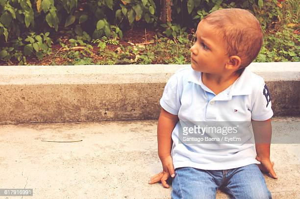 Close-Up Of Boy Sitting On Retaining Wall