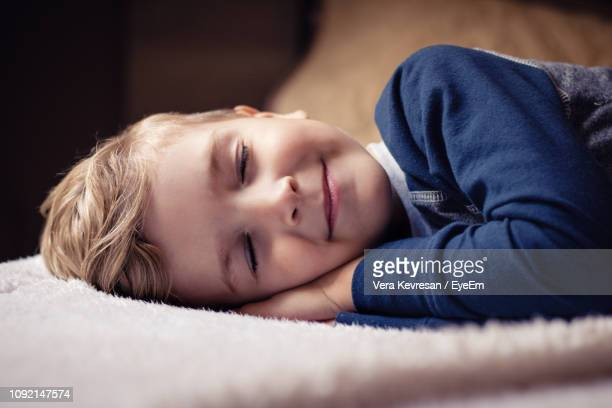 close-up of boy sleeping on bed at home - lying on side stock pictures, royalty-free photos & images