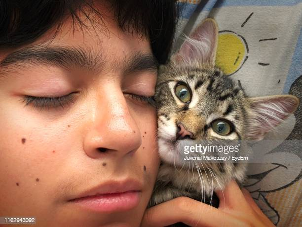 Close-Up Of Boy Sleeping With Kitten