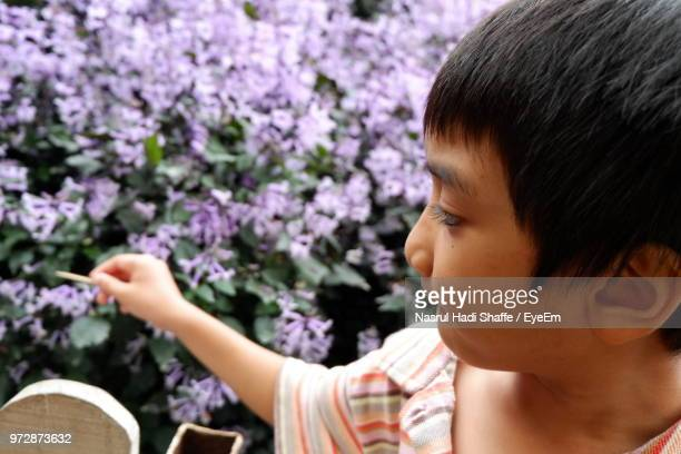 Close-Up Of Boy Standing By Flowering Plants