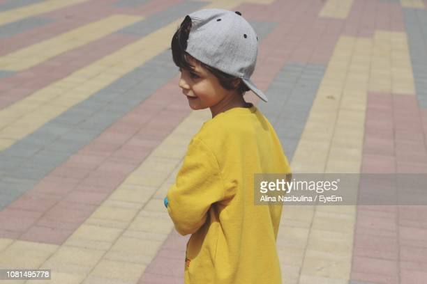 Close-Up Of Boy Standing On Footpath