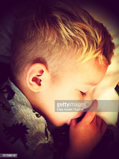 Close-Up Of Boy Sucking Thumb While Sleeping On Bed
