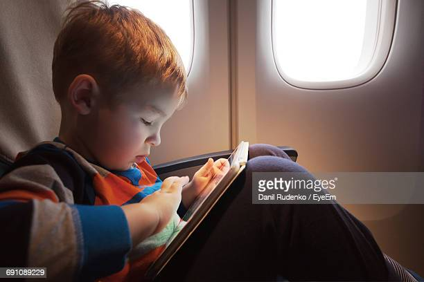 Close-Up Of Boy Using Digital Tablet In Airplane