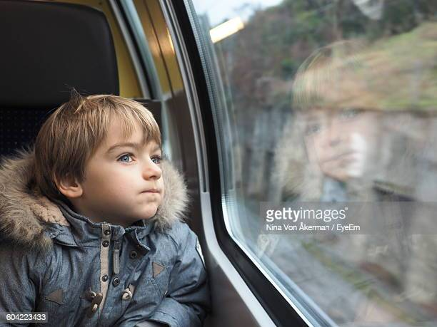 close-up of boy wearing fur jacket looking through car window - kids inside car stock photos and pictures