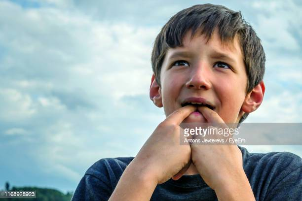 close-up of boy whistling with fingers while standing against sky - whistle stock pictures, royalty-free photos & images