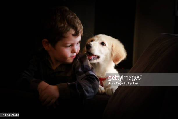 Close-Up Of Boy With Dog On Sofa
