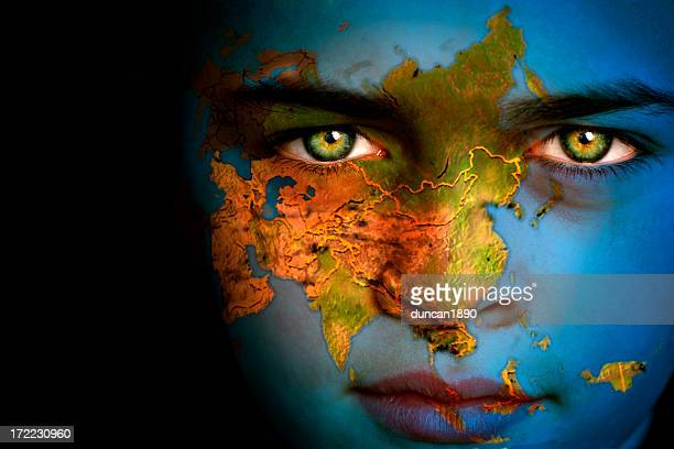 Close-up of boy with Earth map, Asia focus on face