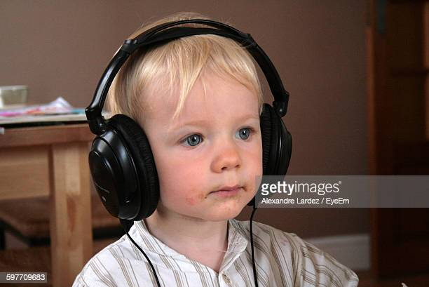 Close-Up Of Boy With Headphones Looking Away At Home