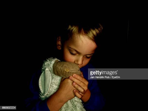 Close-Up Of Boy With Toy Against Black Background