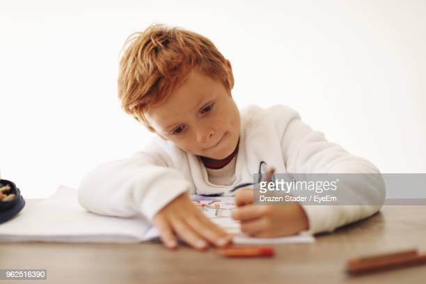 Close-Up Of Boy Writing On Book Against White Background