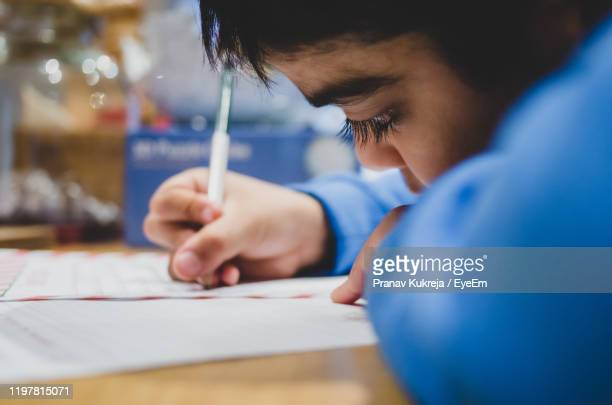 close-up of boy writing on paper at table - leicester stock pictures, royalty-free photos & images