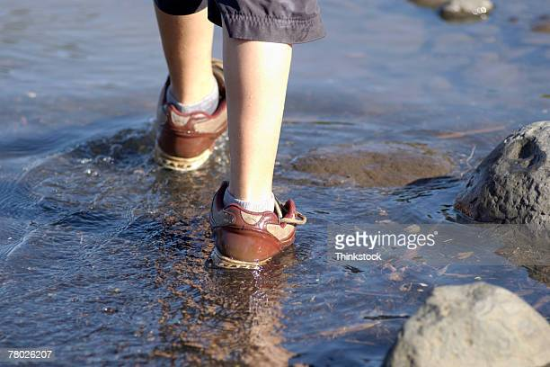 Close-up of boy's legs and red sneakers as he walks away from the viewer in rocky waters near the shore.