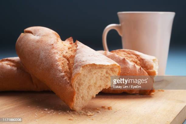 close-up of bread and mug on cutting board against gray background - baguette stock pictures, royalty-free photos & images