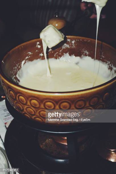 Close-Up Of Bread Dipped In Fondue On Fork
