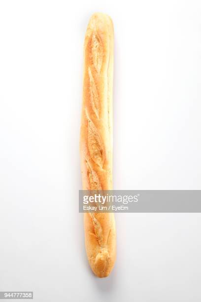 close-up of bread in paper against white background - baguette stock pictures, royalty-free photos & images