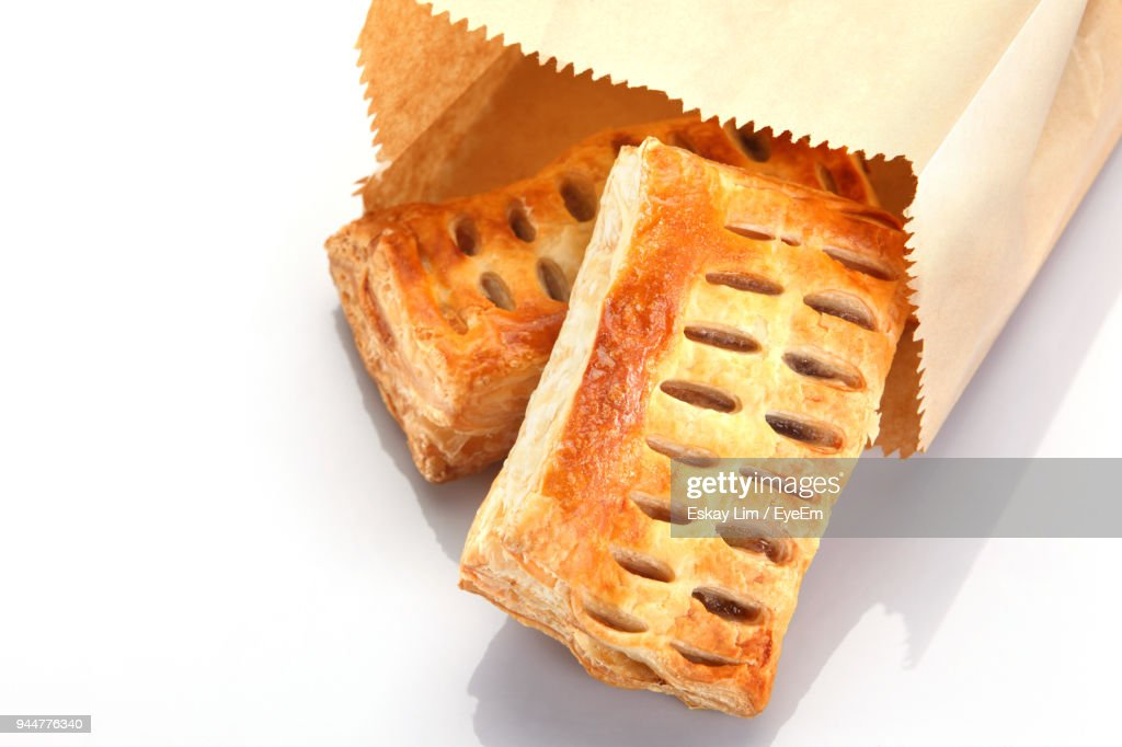 Close-Up Of Bread In Paper Bag Against White Background : Stock Photo