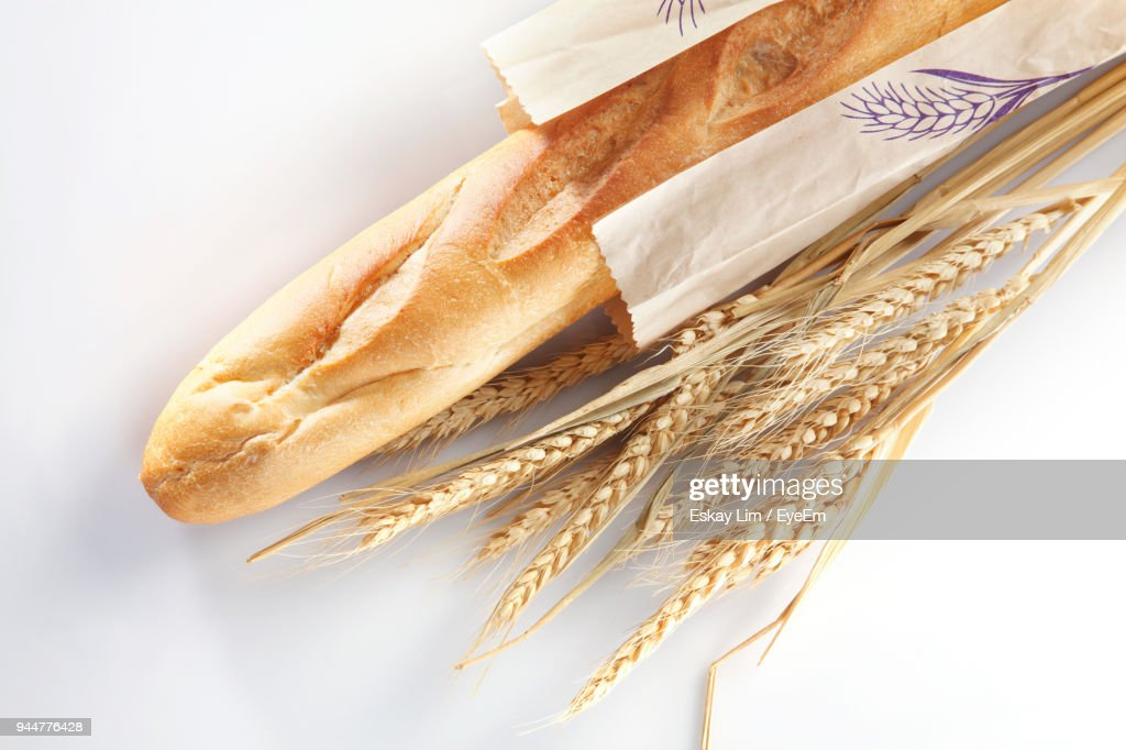 Close-Up Of Bread In Paper With Wheat Against White Background : Stock Photo