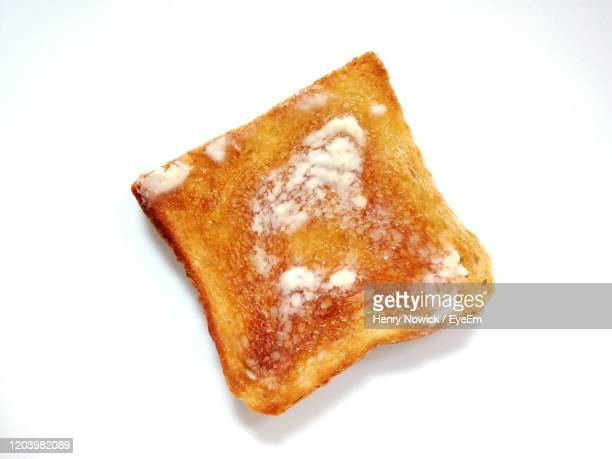 close-up of bread toast with butter over white background - butter stock pictures, royalty-free photos & images