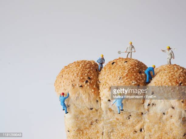 close-up of bread with figurines against white background - human representation stock pictures, royalty-free photos & images