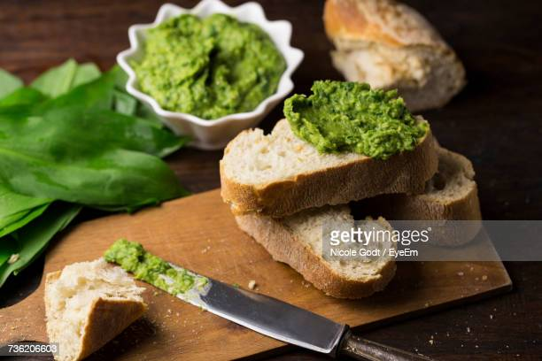 Close-Up Of Bread With Green Paste And Leaves On Wooden Table