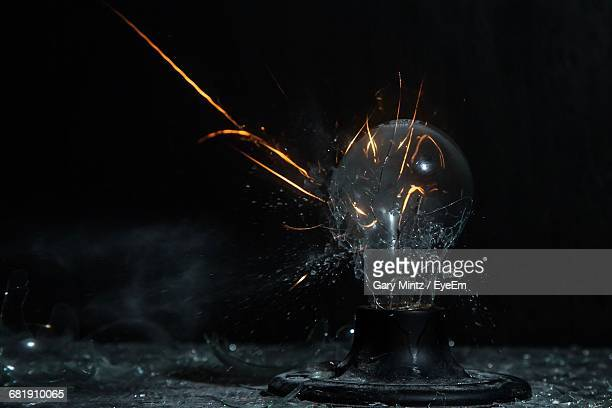close-up of breaking light bulb with copy space - exploding glass stock photos and pictures