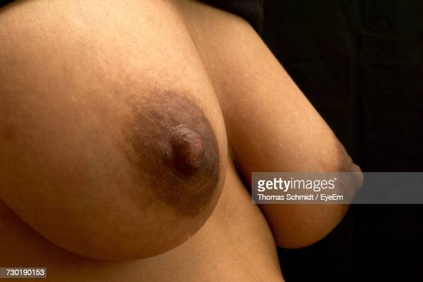 close-up of breast against black background - booby stock pictures, royalty-free photos & images