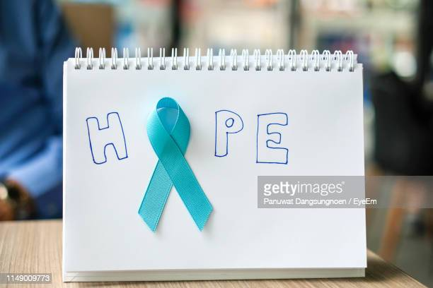 close-up of breast cancer ribbon awareness and text on book - blue cancer ribbon stock photos and pictures