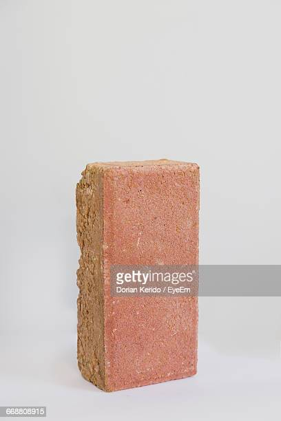 close-up of brick against white background - mattone foto e immagini stock