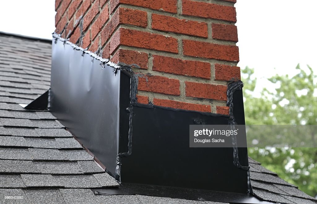 Close Up Of Brick Chimney On House Roof With Medal Flashing Stock Photo
