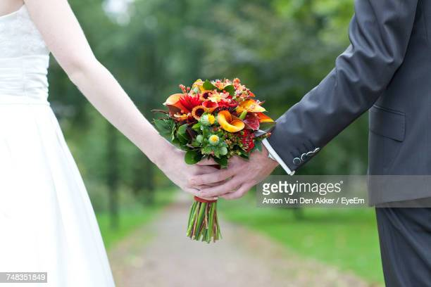 Close-Up Of Bride And Groom Holding Flowers