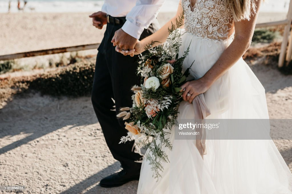 Close-up of bride and groom walking on path at the coast : Stockfoto