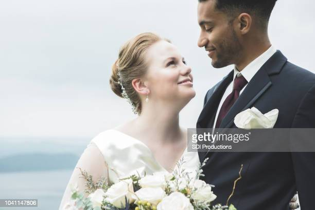 closeup of bride smiling at her groom outdoors - wedding stock pictures, royalty-free photos & images