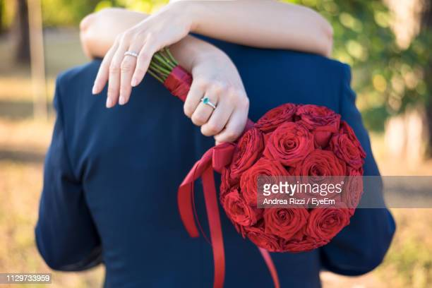 close-up of bride with roses bouquet embracing husband - andrea rizzi stock pictures, royalty-free photos & images