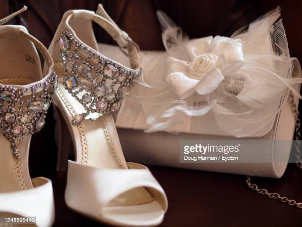 close-up of bride's wedding shoe and her purse behind. - silver shoe stock pictures, royalty-free photos & images
