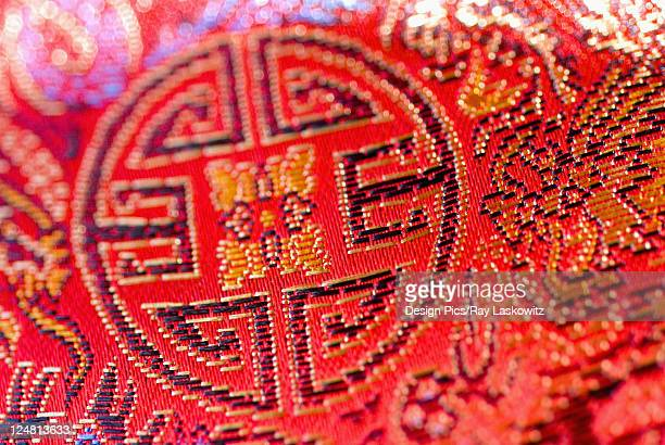 Close-up of bright red cloth with Chinese embroidery.