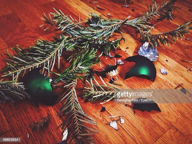 Close-up of broken Christmas bauble and leaves on wooden floor