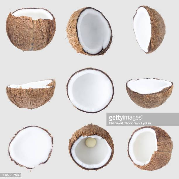 close-up of broken coconuts against white background - coconut stock pictures, royalty-free photos & images