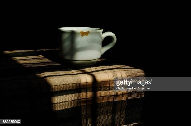 Close-Up Of Broken Coffee Cup Against Black Background
