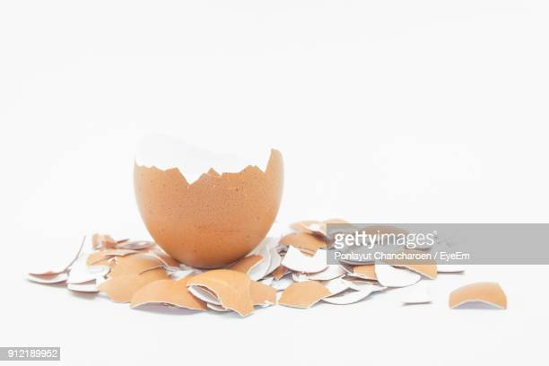 close-up of broken eggshell over white background - eggshell stock pictures, royalty-free photos & images