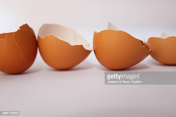 Close-Up Of Broken Eggshells Against White Background
